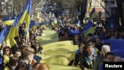 Protestors hold Ukrainian colors in a rally against Russian takeover of Crimea.