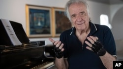 Brazilian pianist Joao Carlos Martins poses for pictures wearing bionic gloves at his home in Sao Paulo, Brazil, Wednesday, Jan. 22, 2020. (AP Photo/Andre Penner)