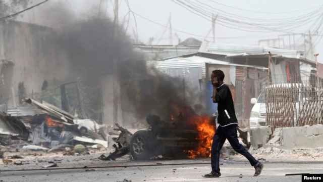 A man talks on his mobile phone as he walks at the scene of an explosion near the entrance of the airport in Somalia's capital Mogadishu, Feb. 13, 2014.