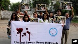 """Members of the social group """"Umeed Jawan Peace Society"""" hold pictures of prominent women's rights activist Sabeen Mahmud, who was killed by unknown gunmen, during a demonstration to condemn her killing, Saturday, April 25, 2015, in Lahore, Pakistan."""