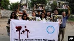 """ບັນດາສະມາຊິກຂອງກຸ່ມສັງຄົມ """"Umeed Jawan Peace Society"""" ຖືຮູບຂອງນັກເຄື່ອນໄຫວເພື່ອສິດທິແມ່ຍິງ ນາງ Sabeen Mahmud ທີ່ຖືກພວກມືປືນຍິງຕາຍ, ວັນທີ 25 ເມສາ 2015 ທີ່ເມືອງ Lahore ປາກິສຖານ"""