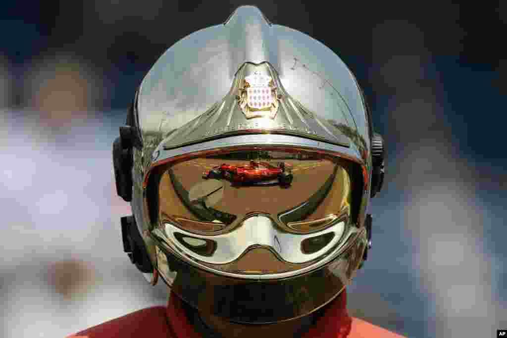 អ្នកបើកបររថយន្តម៉ាក Ferrari ឈ្មោះ Kimi Raikkonen នៃប្រទេសហ្វាំងឡង់ ត្រូវបានឆ្លុះចេញពីមួករបស់អ្នកពន្លត់អគ្គីភ័យម្នាក់អំឡុងការហ្វឹកហាត់នៅ Formula One Grand Prix នៅទីលានប្រណាំងក្នុងប្រទេសម៉ូណាកូ។