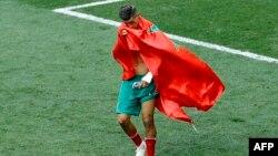 Le Marocain Faycal Fajr couvert du drapeau de son pays quitte le terrain en pleurs après le match du groupe B entre le Portugal et le Maroc lors de la Coupe du monde de football 2018 au stade Luzhniki à Moscou, Russie, m20 juin 2018.