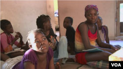 Venise Louis, at far right, joins in watching cartoons at a Haitian orphanage for HIV-positive children.