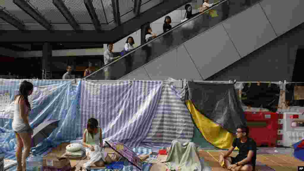 Office workers take an escalator past the pro-democracy student protesters in the occupied areas surrounding the government complex in Hong Kong's Admiralty, Oct. 9, 2014.