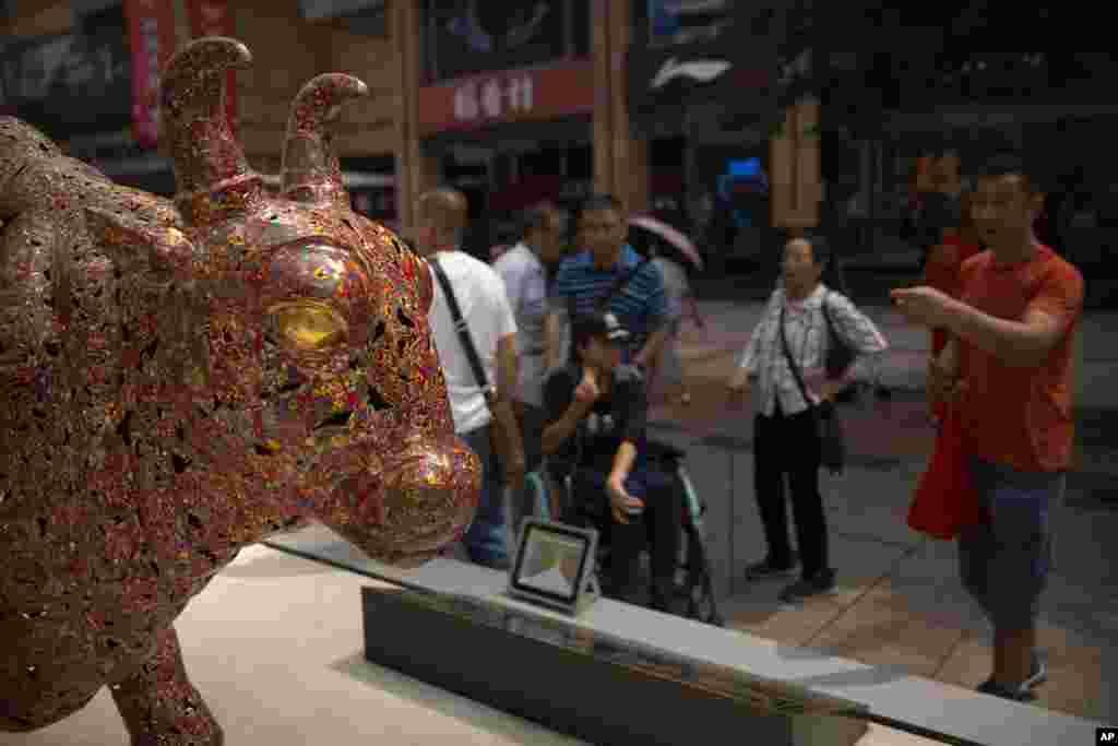 گردشگران در بازار مالی چین؛ بعد از اینکه سالها در بازار وال استریت در نیویورک مجسمه یک گاو وحشی قرار داشت، چین هم مدتی پیش این مجسمه گاو را در بازار مالی خود در پکن قرار داد.