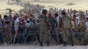 FILE - Turkish soldiers stand guard as Syrians wait behind border fences near the southeastern town of Suruc, Sanliurfa province, Sept. 2014.