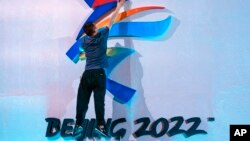 FILE - A crew member leaps to fix a logo for the 2022 Beijing Winter Olympics before a launch ceremony to reveal the motto for the Winter Olympics and Paralympics in Beijing, Sept. 17, 2021.