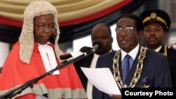 President Robert Mugabe being sworn-in August 22 by Chief Justice Godfrey Chidyausiku