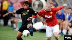 Jonathan dos Santos, Barcelona (kiri) dan Wayne Rooney, Manchester United, dalam sebuah pertandingan bola di tahun 2011.