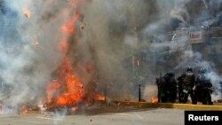 Miembros de las fuerzas de seguridad son atacados por opositores en una calle de Caracas.