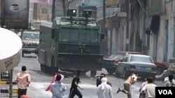 Los manifestantes lanzan rocas contra un vehículo anti motines de las fuerzas del gobierno, usado en las maniobras de represión.