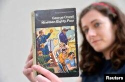 伦敦一家书店女职员手持英国作家乔治·奥威尔著作《1984》。描写集权政府对个人监控无所不在的名著《1984》于1949年6月8日出版,在2013年重回畅销书排行榜。(2013年6月9日)