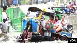Warga mengunakan 'tuk-tuk', semacam becak di Bangkok, untuk melintasi jalanan yang tergenang banjir (7/11).