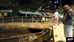 Люди спостерігають за тим як відступає вода у Габрон Харбор, Гонолулу.