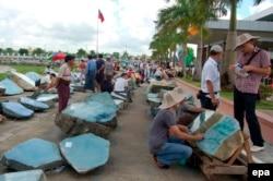 FILE - Gem merchants examine jade at a sale in Yangon, Myanmar, July 3, 2006.