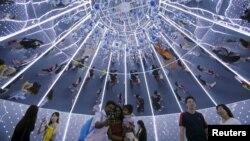 Khách mua sắm chụp ảnh bên trong cây Giáng sinh khổng lồ được trang trí trên đường Orchard, nơi tập trung các cửa hàng mua sắm nổi tiếng của Singapore.