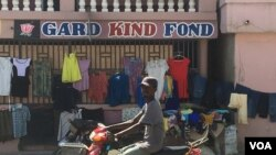 Yon nonm kap pase sou yon motosiklèt devan yon kay roz ki gen boutik prèt a pòte devan li nan Pòdpè.