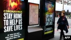 在倫敦市中心,一名行人在有關新冠疫情的標牌前走過。(2020年3月31日)