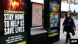 2020年3月31日伦敦市中心行人走过有关冠状病毒的标牌:为拯救生命请呆在家里。