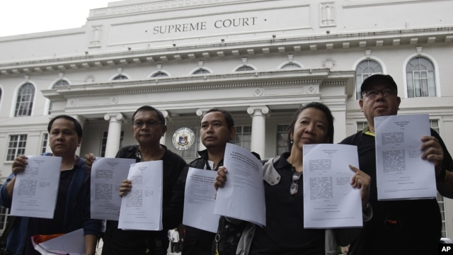 Filipino journalists and some media group leaders hold their petitions against the Cybercrime Prevention Act as they submitted them to the Supreme Court in Manila, October 3, 2012.