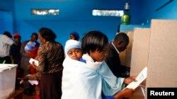 Une femme se rend dans un isoloir pour voter dans un bureau de vote à Gatundu, Kenya, le 4 mars 2013.
