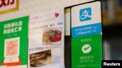 香港一家餐廳外懸掛的阿里巴巴關聯公司螞蟻金服的電子支付服務支付寶,以及騰訊控股所屬的微信支付的標示。