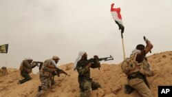 FILE - Fighters from Badr Brigades Shiite militia clash with Islamic State group militants at the front line on the outskirts of Fallujah, Anbar province, Iraq, June 1, 2015.