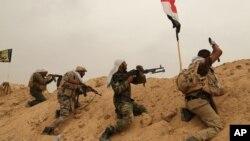"""F什叶派民兵巴德尔旅成员同""""伊斯兰国""""激进分子在安巴尔省费卢杰郊外前线作战。(2015年6月1日)"""