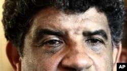 Abdullah al-Senoussi, head of Libyan intelligence, speaks to the press as gunfire erupts all around the Rixos hotel in Tripoli, Libya. (File Photo - August 21, 2011)