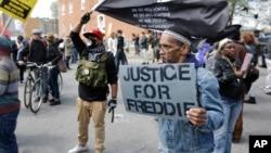 ພວກປະທ້ວງ ເຕົ້າໂຮມກັນຢູ່ນອກ ສະຖານີຕຳຫຼວດແຫ່ງນຶ່ງ ໃນເຂດຕາເວັນອອກ ຂອງກົມຕຳຫຼວດນະຄອນ Baltimore ລັດ Maryland ກອ່ນໜ້າຈະມີການເດີນຂະບວນ ປະທ້ວງການເສຍຊີວິດຂອງທ້າວ Freddie Gray ໃນລະຫວ່າງການຈັບກຸມໂດຍເຈົ້າໜ້າທີ່ຕຳຫຼວດ Baltimore, ວັນທີ 25 ເມສາ 2015.