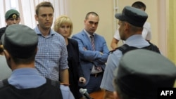Russia's top opposition leader Alexei Navalny (L) stands in the courtroom in Kirov, July 18, 2013.