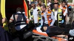 Petugas medis Israel membawa seorang remaja perempuan Palestina pasca serangan penikaman di Yerusalem hari Senin (23/11).