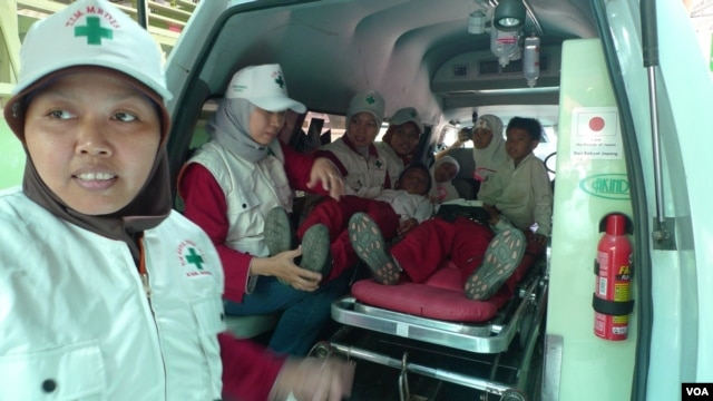 Aid workers and students simulate an earthquake evacuation at Jejeran Islamic Elementary School in Bantul, Central Java, Indonesia, October 22, 2012. (S. Schonhardt/VOA)