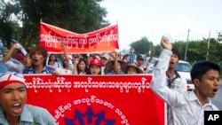 Công nhân làm việc tại nhà máy ở Myanmar giơ áp phích 'Mạng lưới Công nhân Myanmar, Có ít nhất 4.000 kyat một ngày' trong cuộc biểu tình ở thị trấn Hlaingtharyar, ngoại ô Yangon, 12/7/2015.
