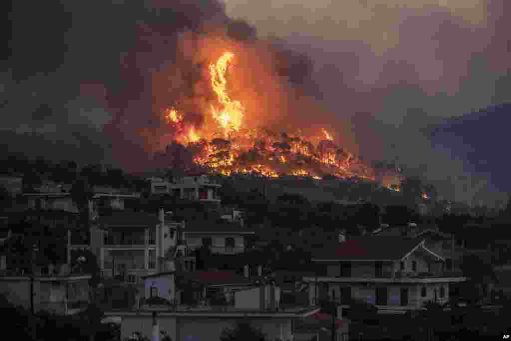Fire burns near the village of Galataki as authorities evacuate the residents near Corinth, Greece, July 22, 2020.