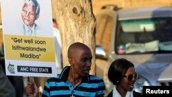 Seguidores del ex presidente Nelson Mandela hacen guardia en las afueras del hospital y permanecen en oración por la salud del líder político.