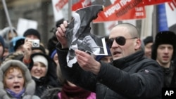 13일 모스크바에서 열린 시위에서 푸틴 대통령의 사진을 찢는 야당 지도자 세르게이 우달초프의 모습