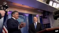 FILE - White House press secretary Sean Spicer, center, is interview by Sean Hannity, left, of Fox News Channel in the briefing room of the White House in Washington, Jan. 24, 2017.