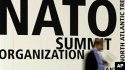 A man walks by signage at the NATO summit venue in Lisbon, Portugal, 18, Nov. 2010. Heads of State of NATO member countries gather for a two day summit beginning Friday.