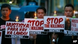 "Protesters hold placards in a candlelight protest against what they say are extrajudicial killings in President Rodrigo Duterte's ""War on Drugs"" campaign, in suburban Quezon city, northeast of Manila, Philippines, Oct. 8, 2016. HRW says Duterte had ""steamrolled human rights protections and elevated unlawful killings of criminal suspects to a cornerstone of government policy."""