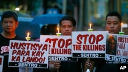 """FILE - Protesters hold placards in a candlelit protest against extrajudicial killings in President Rodrigo Duterte's """"War on Drugs"""" campaign in suburban Quezon city, northeast of Manila, Philippines, Oct. 8, 2016."""
