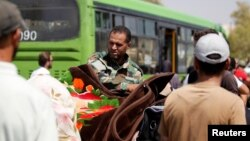 FILE - A Syrian army soldier inspects people's belongings before their evacuation from Damascus suburb of Mouadamiya, under an agreement between rebels and Syria's army, Sept. 8, 2016.
