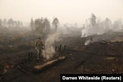 Seorang tentara memeriksa kebakaran lahan gambut di dekat Palangka Raya, Kalimantan Tengah, 28 Oktober 2015. (Foto: REUTERS/Darren Whiteside)