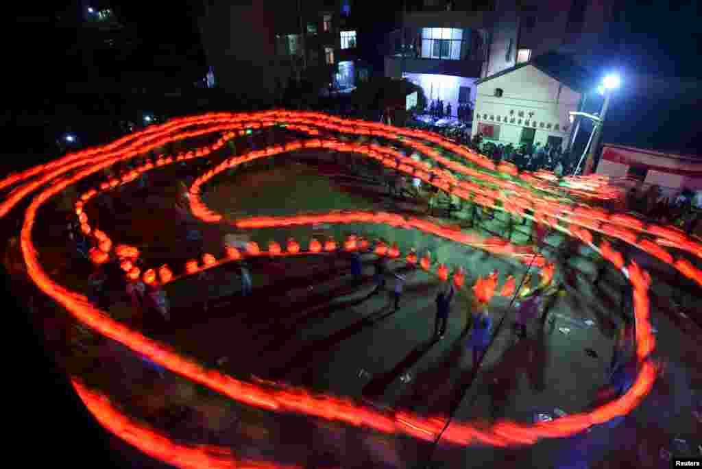 کودکان در یک جشنواره چینی با نور بازی می کنند.