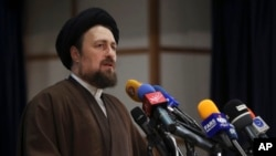 FILE - Hassan Khomeini, grandson of the founder of Iran's Islamic Republic, Ayatollah Khomeini, speaks at the election headquarters of the Interior Ministry after registering his candidacy for the Feb. 26 Assembly of Experts elections in Tehran, Iran, Dec