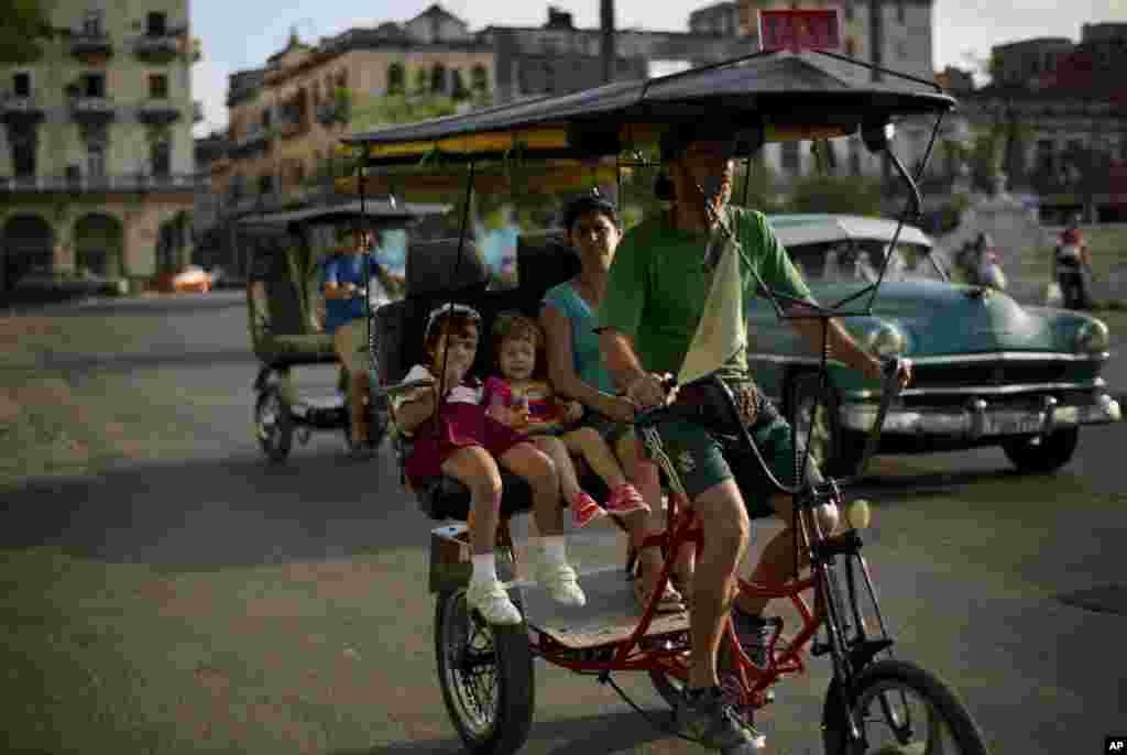 زنی با دو دهنربچه سوار بر ريکشا از خيابانهای مرکز هاوانا در ۲۹ دی ۱۳۹۳ (۱۹ ژانويه ۲۰۱۵) میگذرد. تاکنون کوبا به آهستگی به جمع شدن تحريمهای آمريکا عکس العمل نشان داده است. هاوانا میگويد از بسته پيشنهادی برقراری کامل روابط با ايالات متحده استقبال میکند، اما اصرار دارد که کنترل تک حزبی بر روند سياسی کشور و برنامه ريزی مرکزی برای اقتصاد ادامه خواهد داشت.