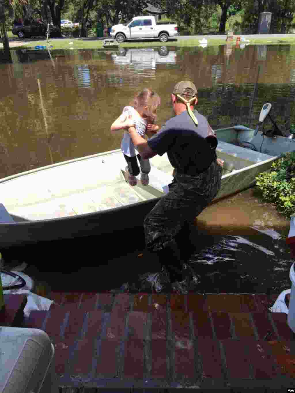 Graham Kinchen of St. Amant, Louisiana, takes time off to give his daughter a boat ride — in their front yard. (M. Melton/VOA)