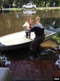Graham Kinchen of St. Amant, Louisiana, takes time off to give his daughter a boat ride — in their front yard. (D. Kinchen/VOA)