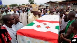 FILE - In this Sunday, May 24, 2015 file photo, men carry the coffin of UPD-Zigamibanga party leader Zedi Feruzi during his funeral in Bujumbura, Burundi. Independent experts should investigate Burundi forces for alleged human rights violations including extra-judicial executions, rape and looting during the deadliest day in the months of unrest over President Pierre Nkurunziza's extended tenure, an international human rights group has said.